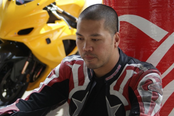 Motorcycle rider taking a breather at the track
