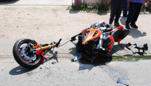 A motorcycle destroyed in an accident featuring broken  forks and tripleclamp