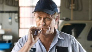 an unintelligent looking mechanic who appears to be smoking drugs, emphasizing a person's right to choose their own mechanic after an accident