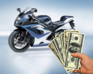 a hand holding lots of money, apparently received from the insurance company for a rental motorcycle during the repair time