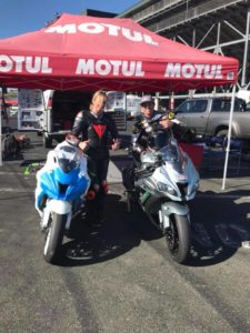 Tyler and AJ posing for a photo with their motorcycles under the Motul EZ Up during a track day