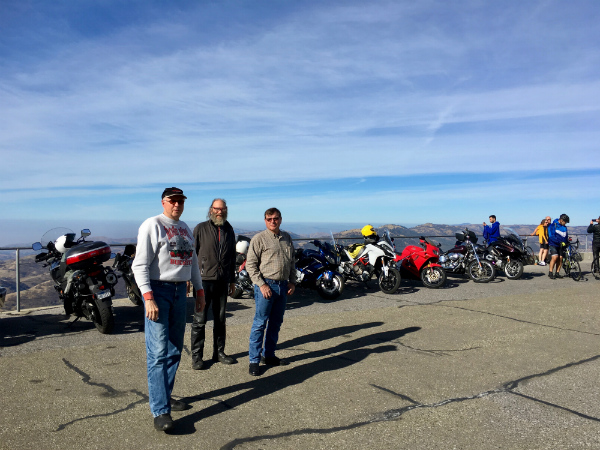 many adventure riders standing together with their motorcycles parked in the background and a beautiful mountain skyline in the far back