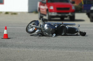 Scene of motorcycle accident with caution cone set up and silver motorcycle damaged, laying on it's side