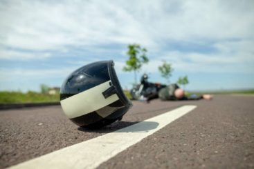 helmet laying on the road in the foreground, motorcyclist laying in the road in the background, apparently he has been in an accident