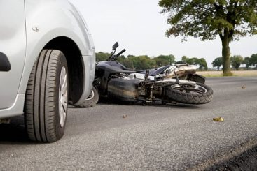 a dual sport motorcycle laying on its side after being hit by a car