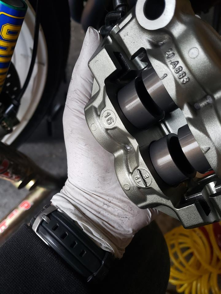 closeup of racing calipers held by mechanic for inspection