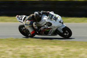 Female Racer AJ hitting the apex on her RiderzLaw Racing ZX10R