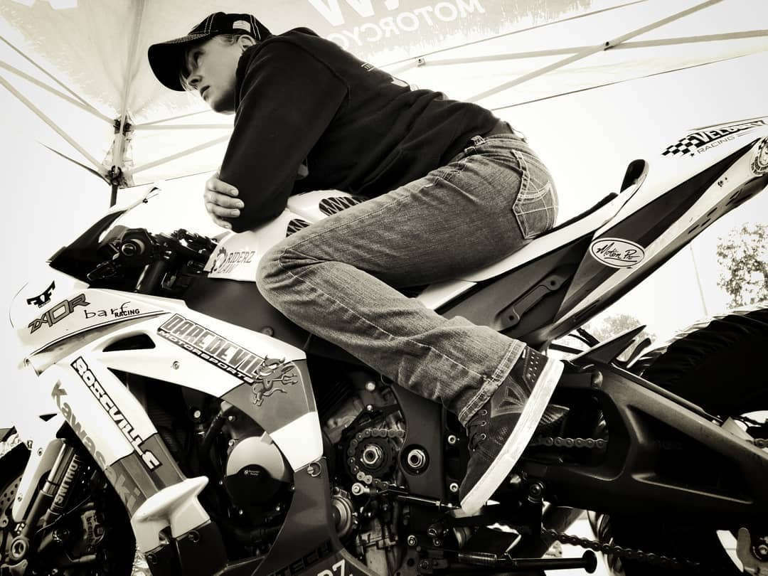 Female motorcycle racer AJ sitting on her ZX10 in the pits, preparing for Femwalla all female motorcycle race at Chuckwalla
