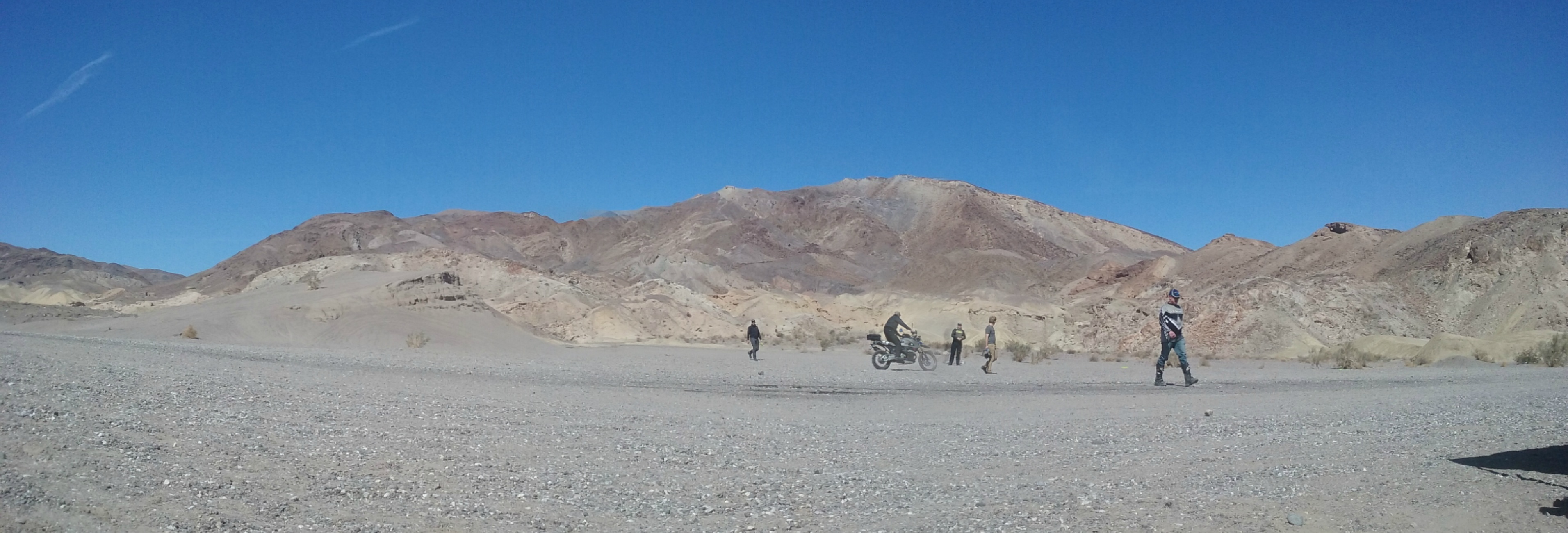 wide view of barren desert with dual sport riders on a motorcycle in the distance