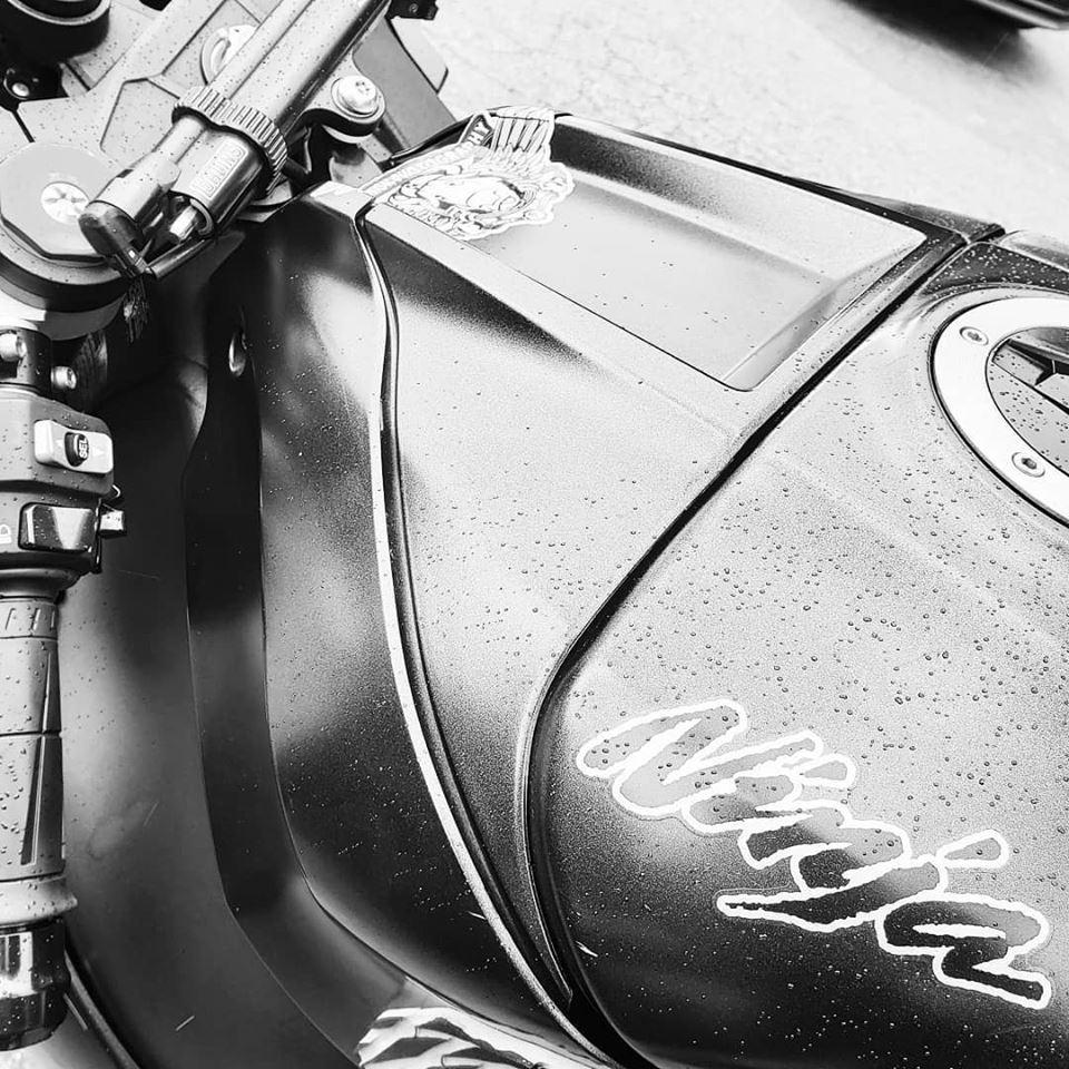 black and white closeup of Kawasaki Ninja gas tank in the rain