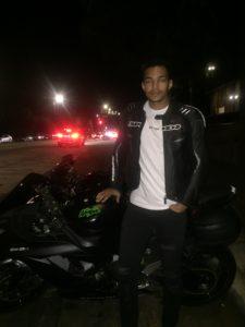 young man standing next to Kawasaki Ninja wearing Spidi armored jacket