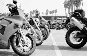 Black and white- variety of motorcycles parked outside the International Motorcycle Show in California