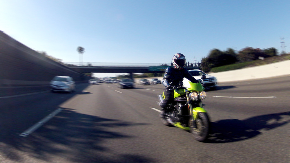 green Triumph Speed Triple motorcycle on the highway in focus with a blurry background