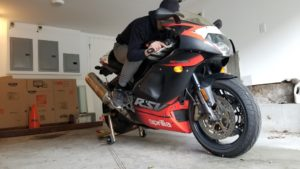 Black and red Aprilia Motorcycle on rear stand with rider in tucked position