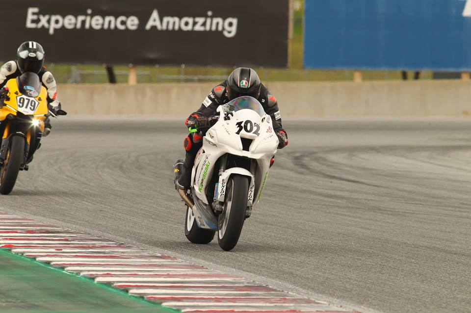 AJ tucked behind her Kawasaki ZX10 motorcycle accelerating into the front straight at Laguna Seca