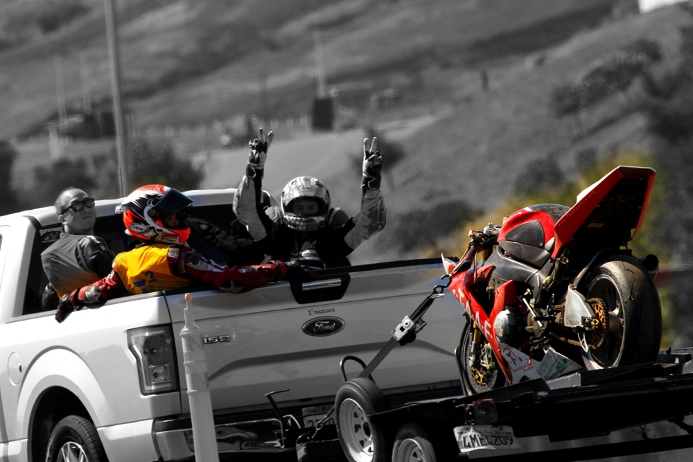 "stylized image of a motorcycle damaged from a track accident loaded onto the trailer, and the rider signalling ""victory"" with both hands raised"