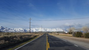 Motorcycle ride on a 2 lane highway with snow capped mountains in the distance