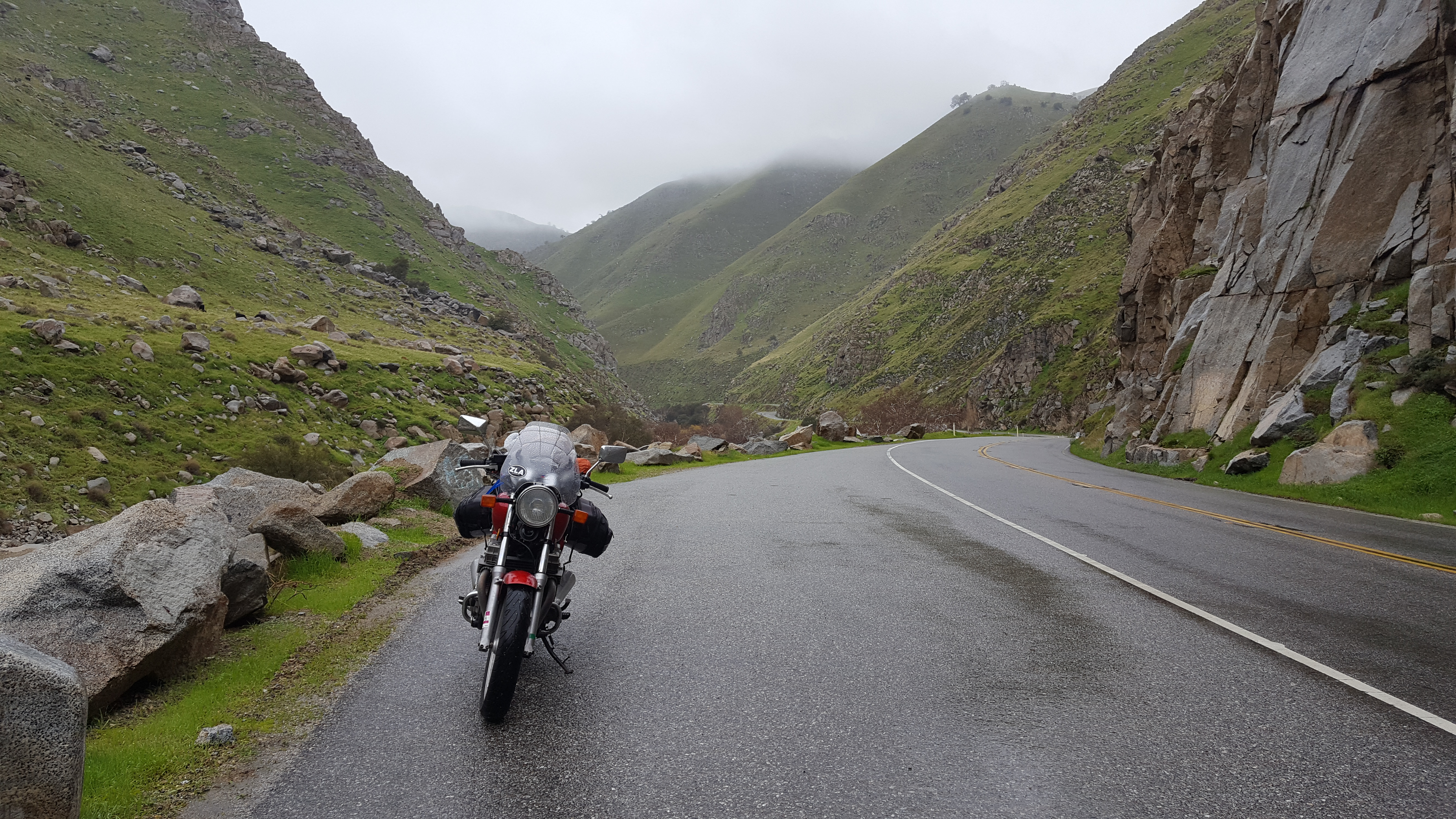 Motorcycle parked roadside on a 2 lane highway with rocky hills and foggy mountain peaks