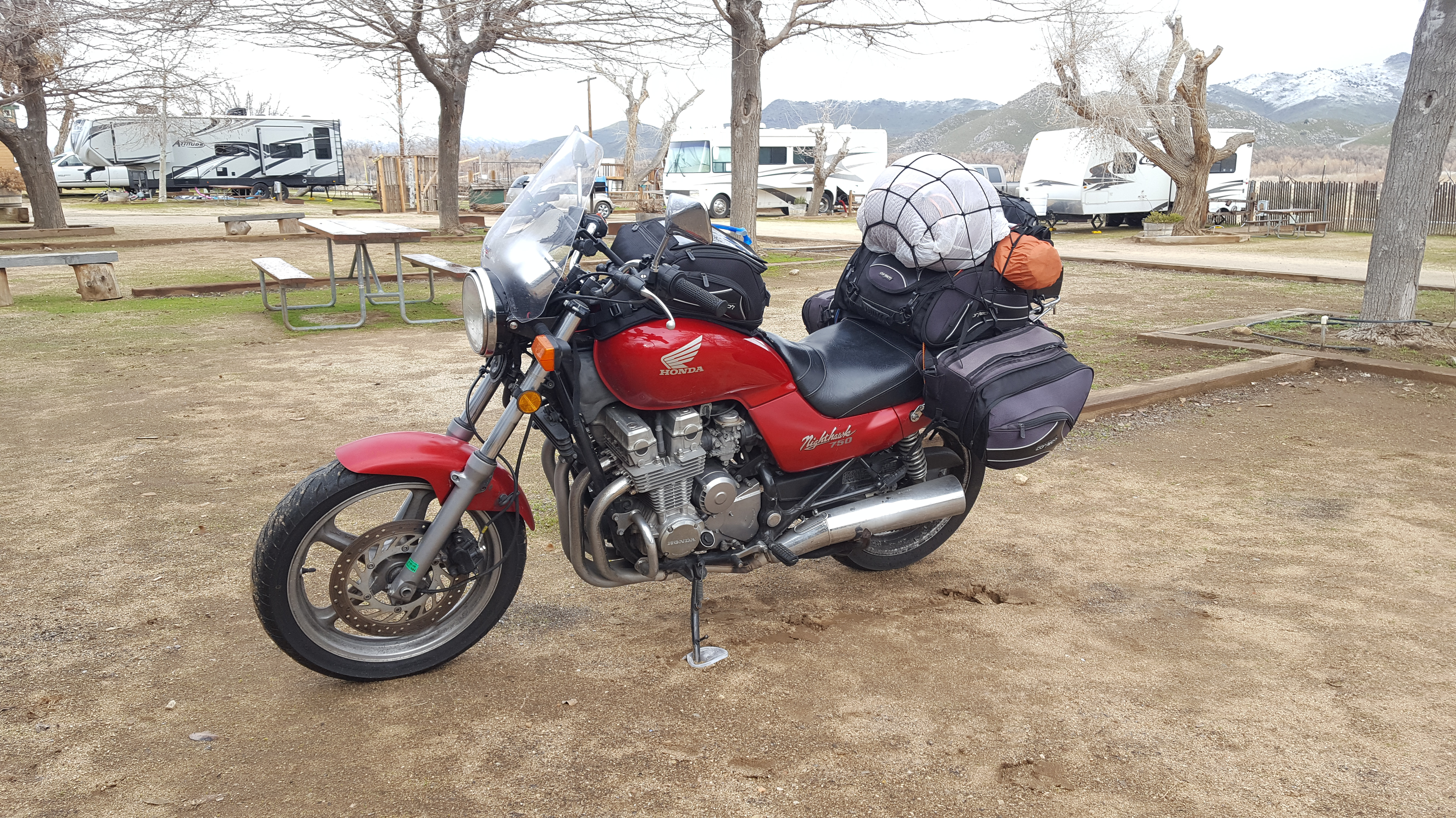 Red Honda Nighthawk fully ready for touring with a windshield, saddle bags, trunk bag, tank bag, and other goodies strapped to it