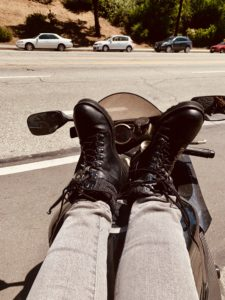 Rider lounging with feet up on the motorcycle tank off the side of the road