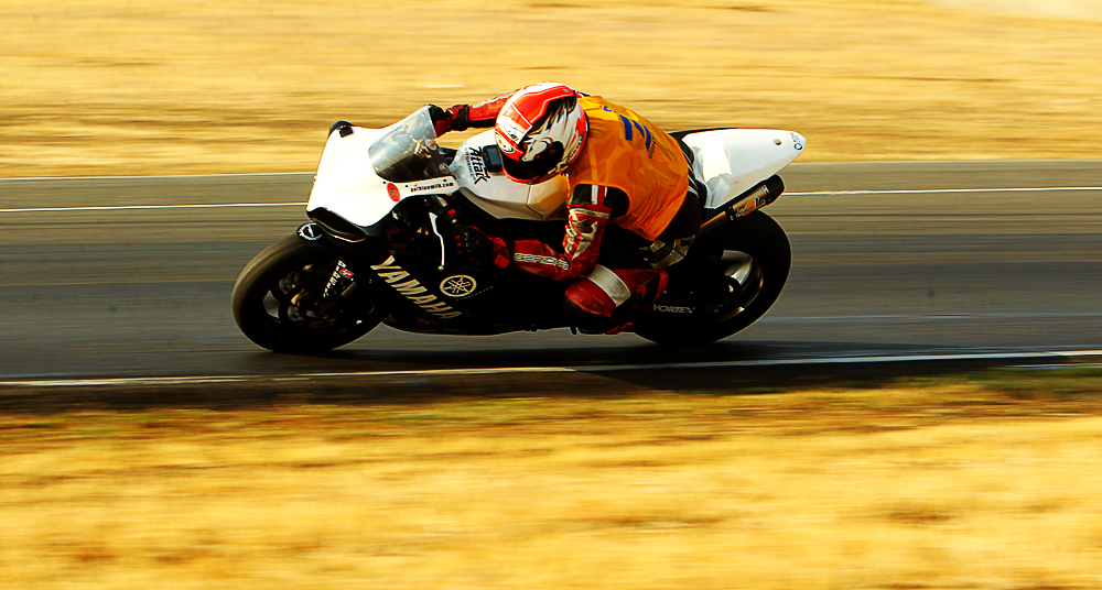 RiderzLaw Motorcycle Racer Dennis Dumapias riding at high speeds on the track
