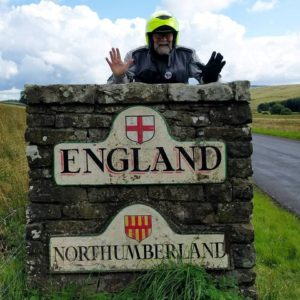 "Adventure Rider next to ""welcome to England"" sign"