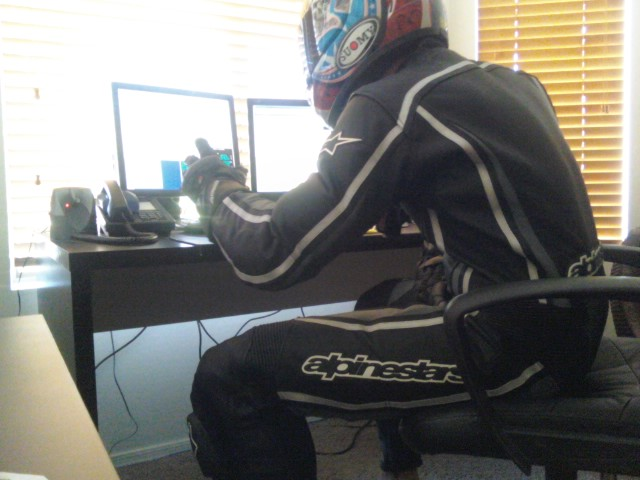 Motorcycle Rider Sitting at a desktop workstation in full leathers and a helmet, a comedic way to show a desire to ride motorcycles.