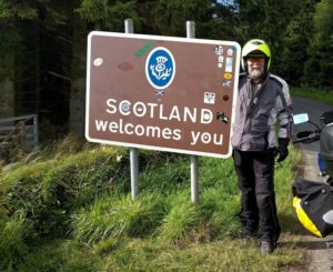 "Adventure Rider standing next to ""Welcome to Scotland"" sign"