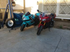 Two motorcycles- one a baby blue triumph, the other a red Yamaha- parked outside on the driveway