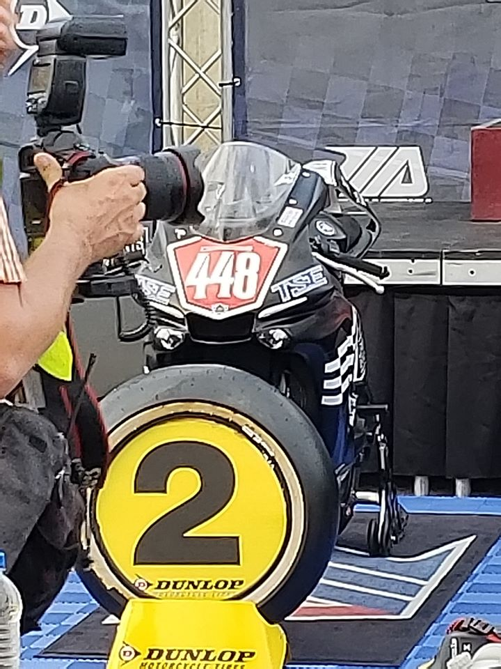 Winner's Circle at MotoAmerica race- closeup of photographer and second place motorcycle